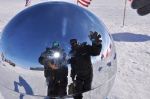 Us reflected in the ceremonial pole with 12 flag around