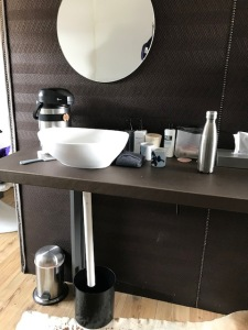 The vanity area in our room. Warm water comes through the dispenser into the sink, then down the drain and into the bucket. Not great, but it works.