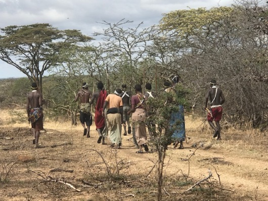 The Hadzade people turn and walk down the road singing